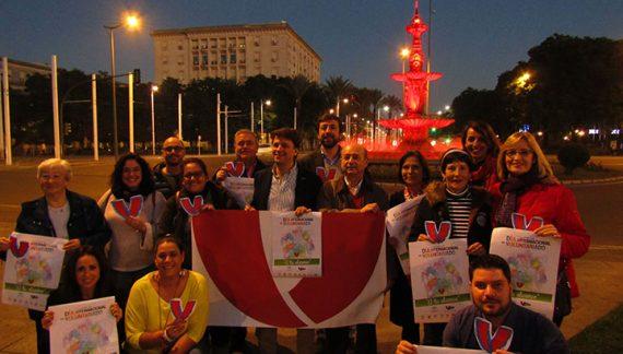 La fuente de las Cuatro Estaciones se ilumina de rojo por el Día Internacional del Voluntariado