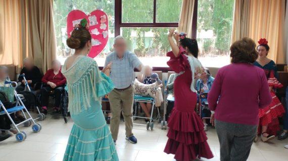 Jóvenes voluntarias se visten de flamenca para acercar la alegría de la Feria a los mayores