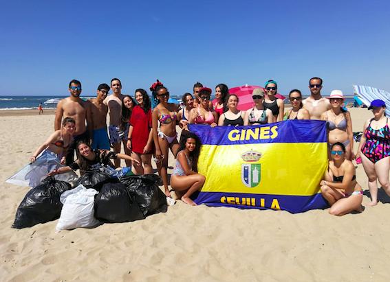 Jóvenes de Gines y Valencina aprovechan su visita a la playa para hacer una acción medioambiental