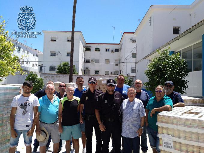 Agentes de la Policía Nacional colaboran con la Asociación de Vecinos Tres Barrios en el reparto de alimentos