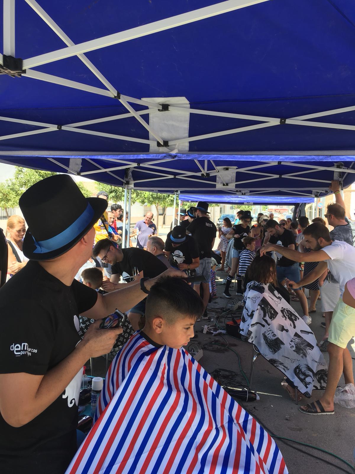 Herrera corta el pelo a sus vecinos en beneficio de Gancho Infantil