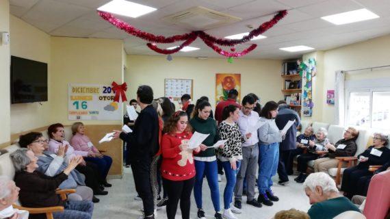 Jóvenes sevillanos visitan a mayores de un centro de día en la Buhaira para cantarles villancicos por Navidad